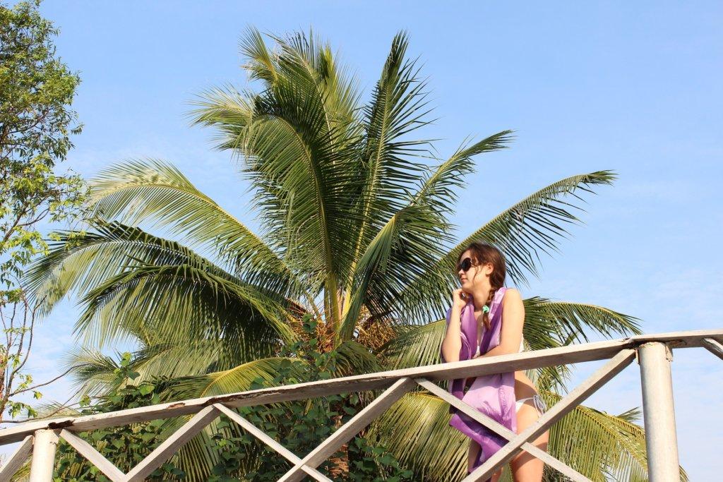 Távolban egy bikinis hölgy, előtérben pálmafák